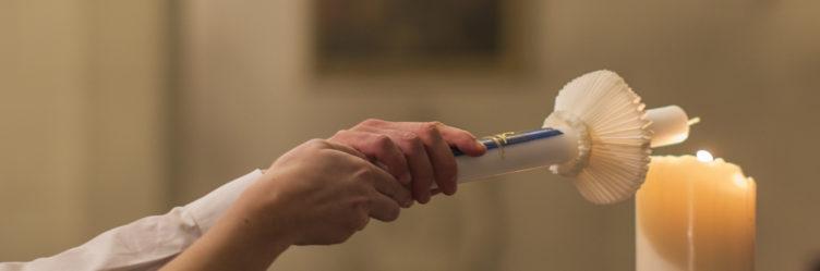 Taufpaten zünden die Taufkerze an der Osterkerze an