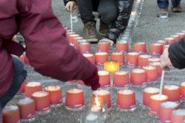 Menschen zünden im Zeichen der Solidarität Kerzen an